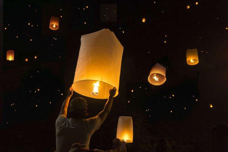 Low angle view of man releasing paper lantern at night