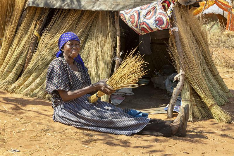 Full length of woman sitting on farm