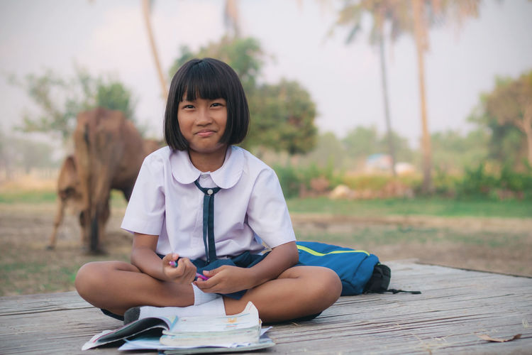 Portrait of smiling schoolgirl studying outdoors