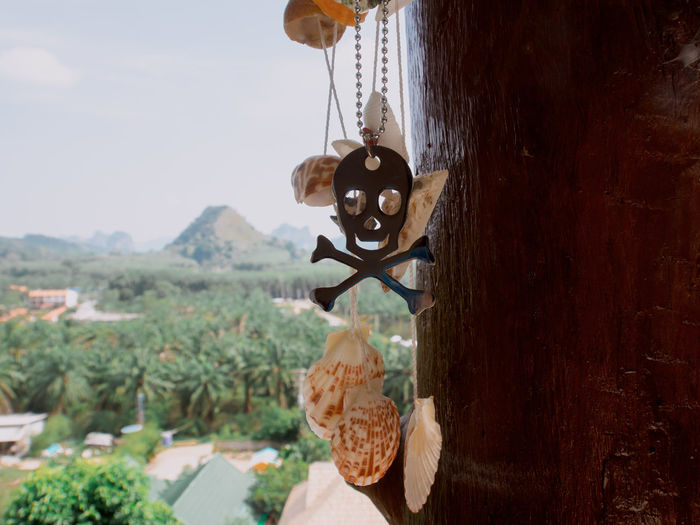 Close-up of bell hanging on rope against sky