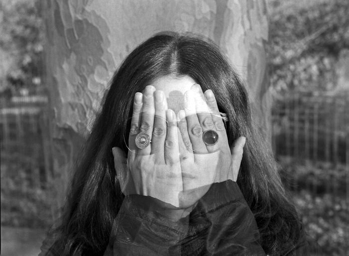 Double exposure image of woman covering face outdoors