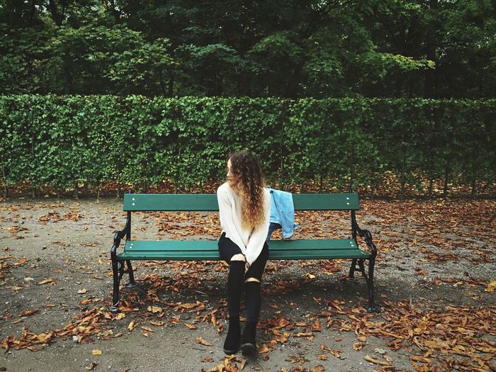 Full length of young woman wearing torn jeans sitting on bench at augarten