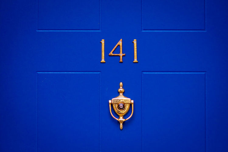 House number 141 on a blue wooden front door