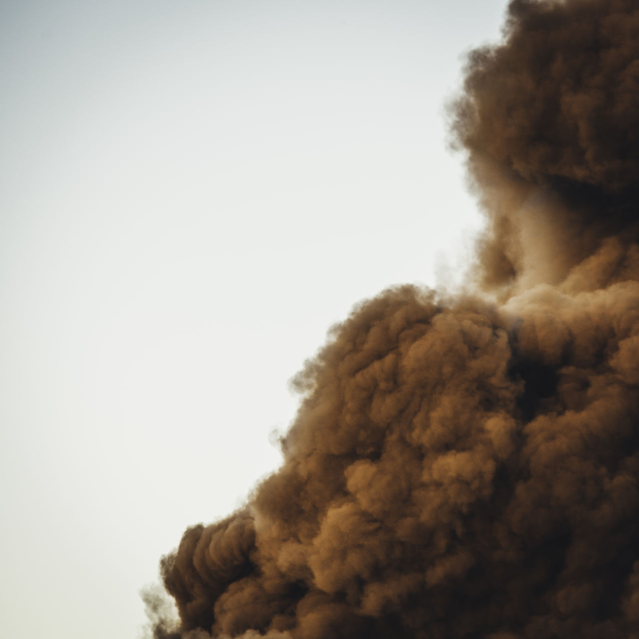 Low angle view of smoke explosion against clear sky