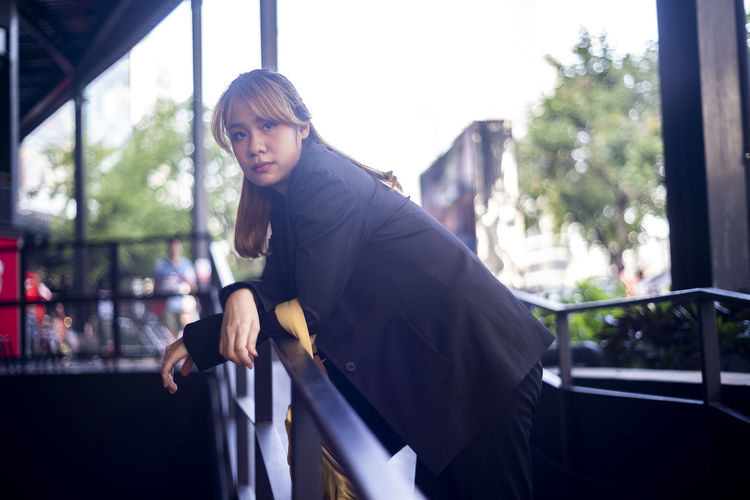 Portrait of businesswoman standing by railing in city