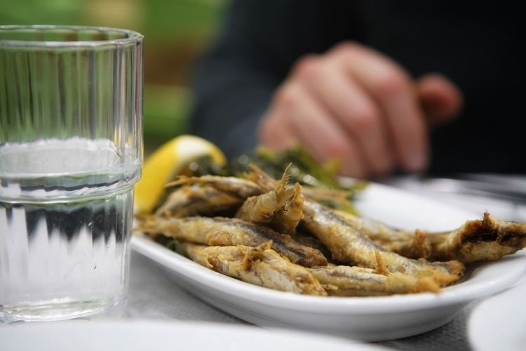 Fried Sardines // Greek Seafood Starter Appetizer Tapas Meze Greek Cuisine Greek Sea Sardellen Sardines Anchovies Fried Anchovies Seafood Food And Drink Drinking Glass Focus On Foreground Human Hand Food Drink Freshness Plate Serving Size Human Body Part Healthy Eating Close-up Water