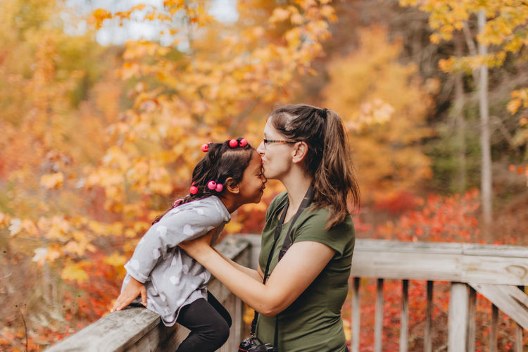 Mother embracing with daughter while standing against autumn trees