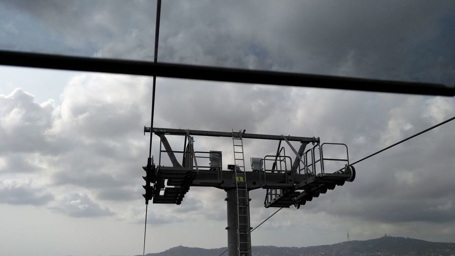 Low angle view of ski lift against cloudy sky