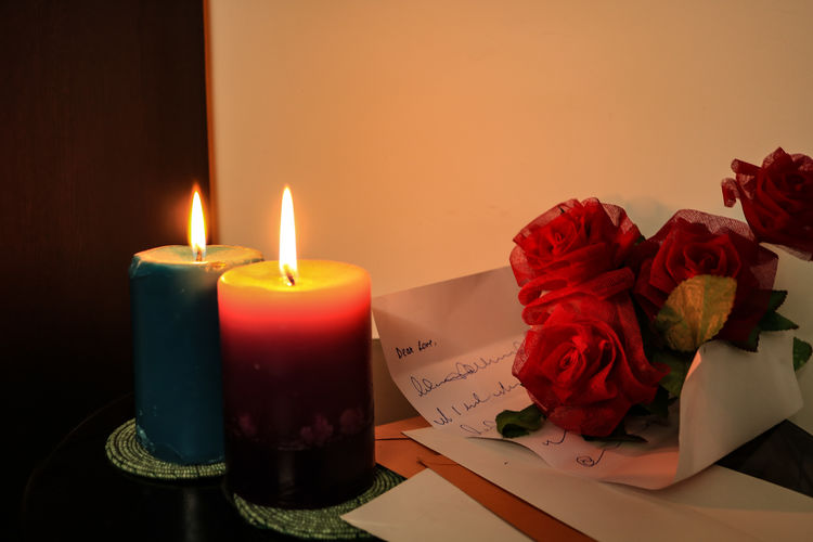 Close-up of rose with candles on table