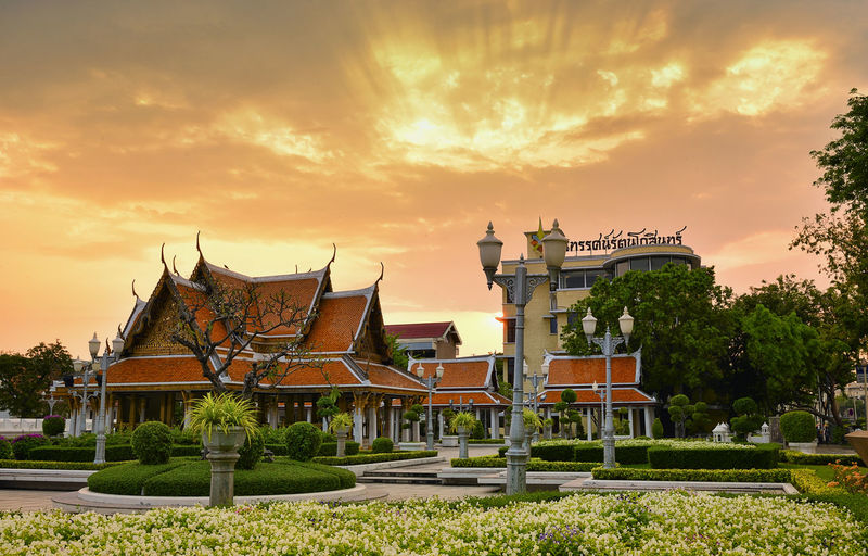 tropical swimming pool at night and Buddhist Temple in thailand Sky Architecture Built Structure Sunset Building Exterior Cloud - Sky Building Plant Belief Nature Religion Place Of Worship Spirituality Tree No People Grass Orange Color Outdoors Travel Destinations Ornate