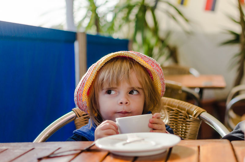 Girl holding coffee cup while sitting in cafe