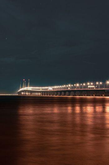 Illuminated bridge over sea against sky at night , penang second bridge