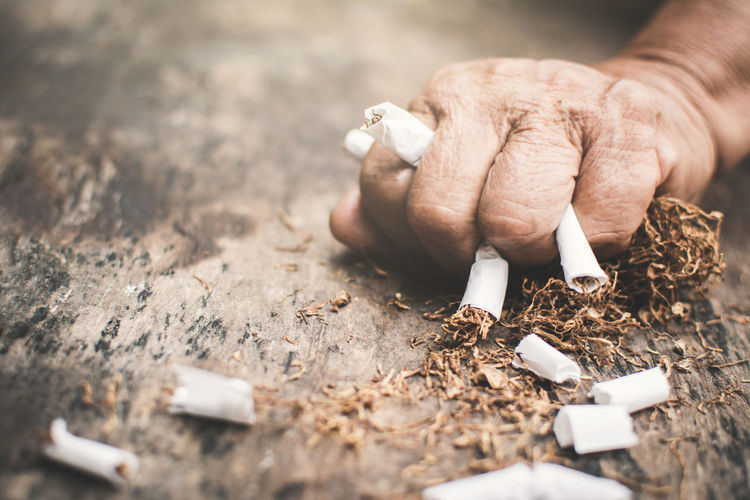 Cropped Image Of Hand Crushing Cigarettes