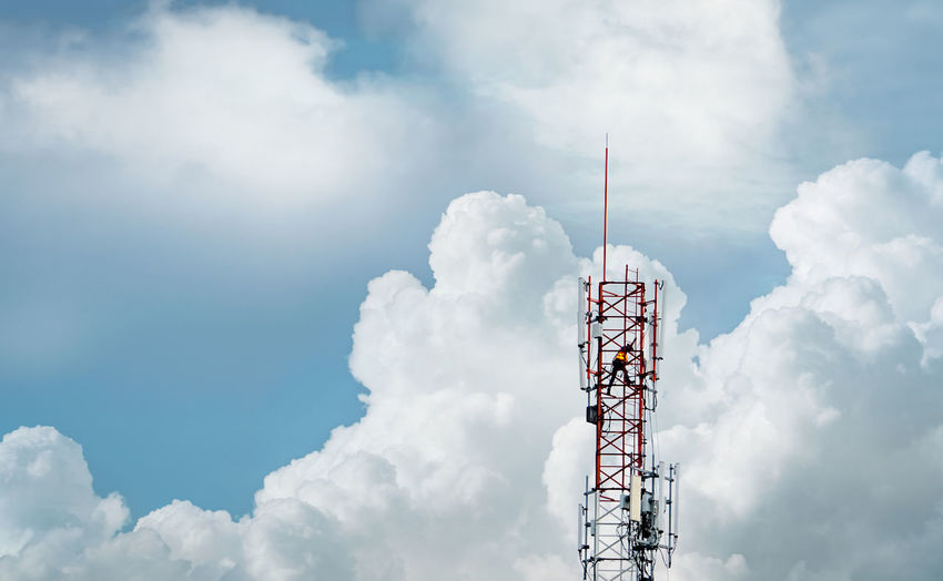 Telecommunication tower with blue sky and white clouds. worker installed 5g equipment.