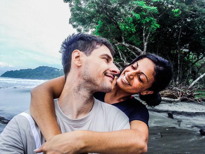 Smiling girlfriend embracing boyfriend at beach