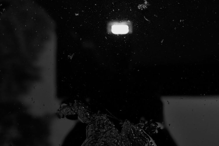 Close-up portrait of man holding illuminated water at night