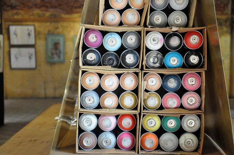 Close-Up Of Colorful Aerosol Cans In Box On Table