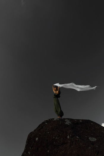 Side view of woman standing on rock against gray background