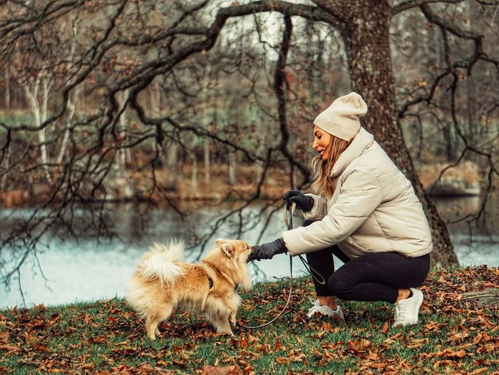 Full length of woman with dog against trees during winter