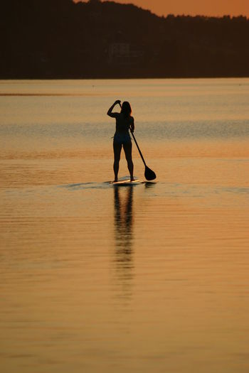 Silhouette woman paddleboarding at sea against sky during sunset