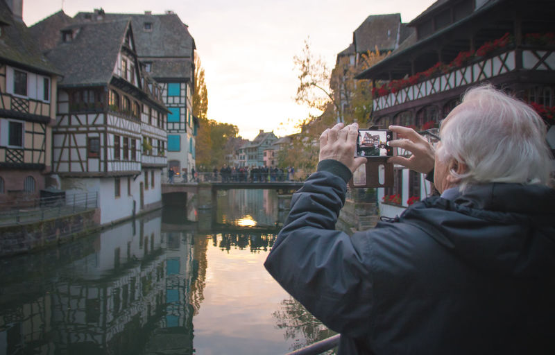 Mature man photographing buildings and canal in city