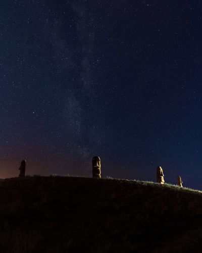 Stone heads on the hill at summer night with visible milky way galaxy