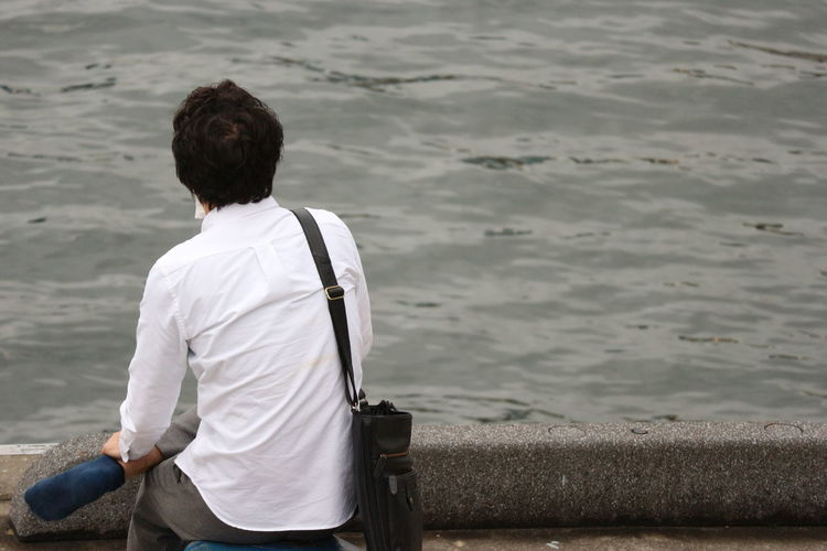 a asian man looking the curve on sea water alone Alone Asian  Backside Lonely Man Relaxing Sitting Thinking Casual Clothing Clam Day Emotion Feelings Leisure Activity Lifestyles Men Nature One Person Outdoors People Real People Rear View Sea Seriously Water