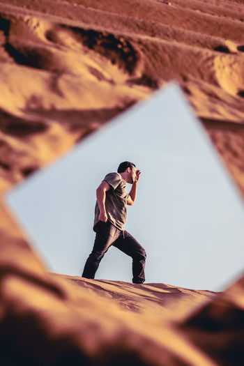 Reflection of man walking on sand in mirror