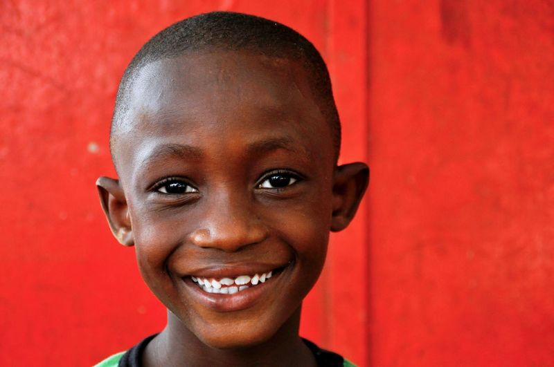 Portrait of smiling boy against red wall