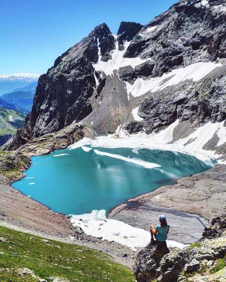 Man looking at lake by mountain