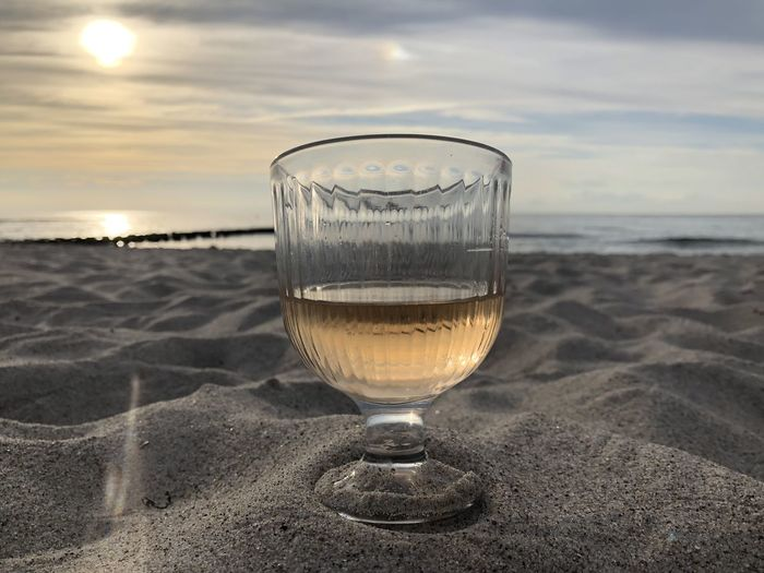 Glass of water on beach against sky during sunset