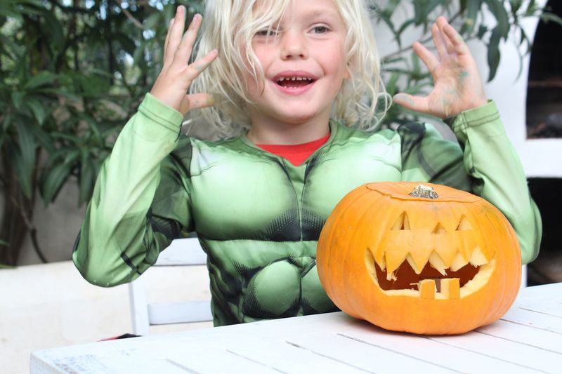 Boy in costume with jack o lantern on table