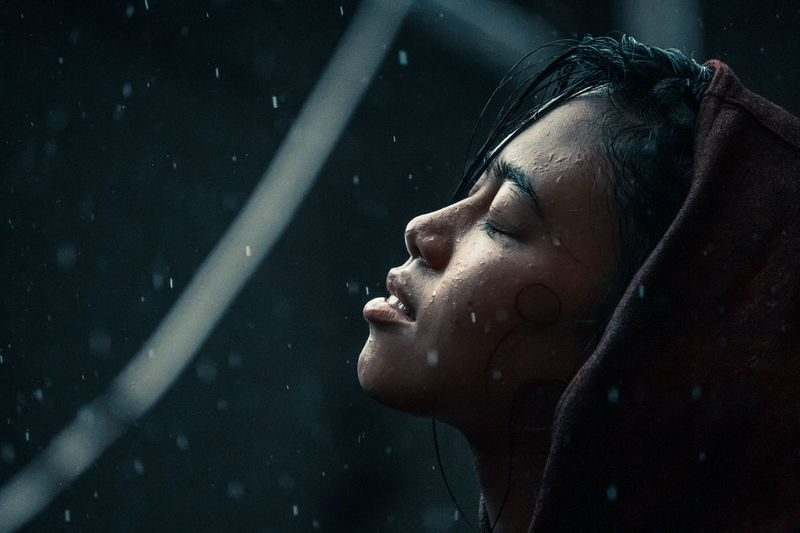 Close-up portrait of young woman with eyes closed in the blue rain