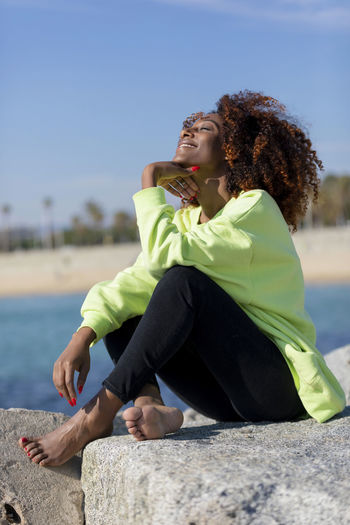 Side view of beautiful curly afro woman sitting on breakwater rocks laughing while resting hand under chin eyes closed outdoors One Person Sitting Leisure Activity Water Lifestyles Nature Casual Clothing Young Adult Full Length Day Sky Real People Curly Hair Relaxation Sunlight Women Focus On Foreground Hair Outdoors Hairstyle Beautiful Woman Woman African American Afro Denim Happiness Happy Fun Daylight Sunlight