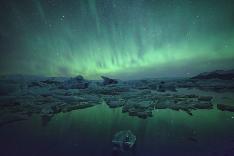 Icebergs in lake against sky at night