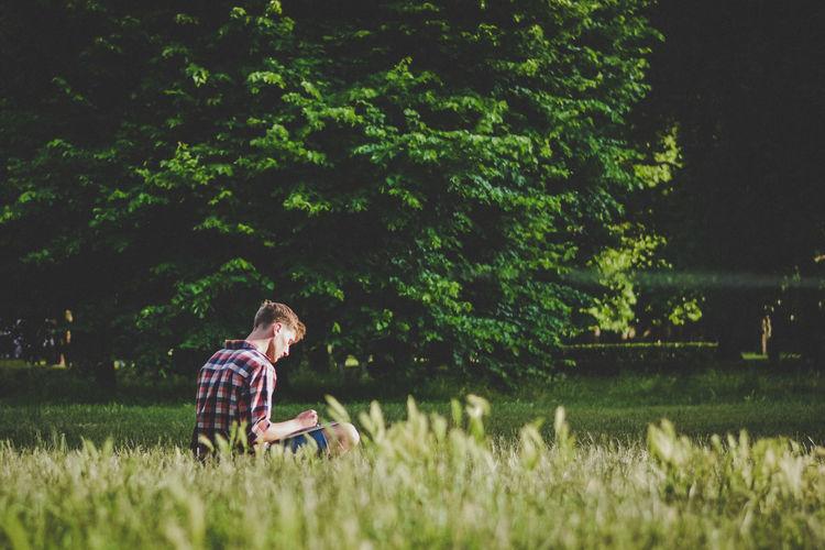 Man sitting on grassy land at park
