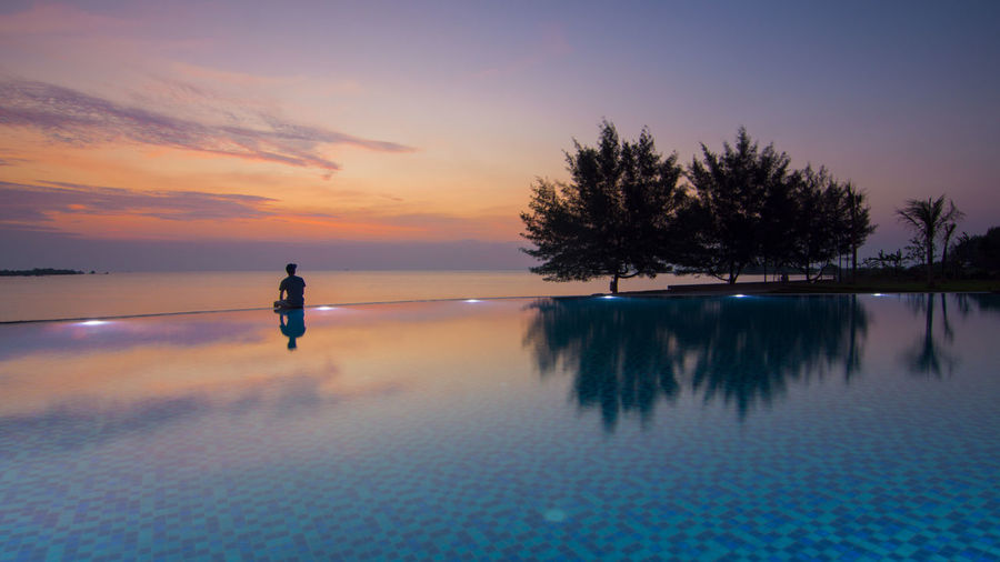Silhouette person looking at sea while sitting on poolside against sky during sunset
