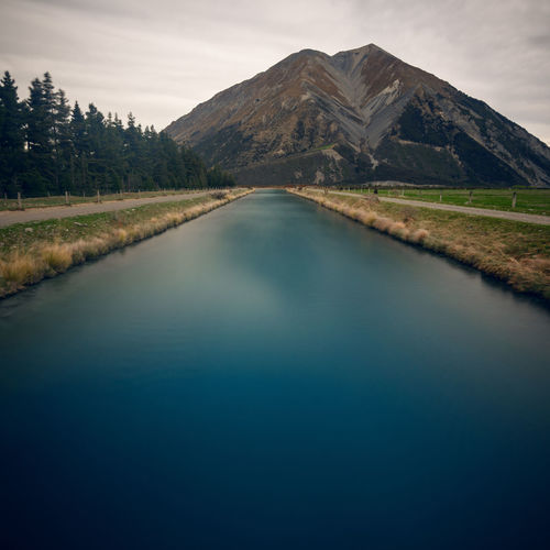 Long exposure from a bridge over the wilberforce canal in direction to mt oakden Beauty In Nature Blue Canal Canterbury Landscape Lines Long Exposure Longexposurephotography Mood Mountain Mt Oakden Nature New Zealand No People NZ Outdoors Scenics South Island Stream Trees Water