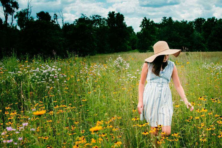 Girl standing by flowers in field
