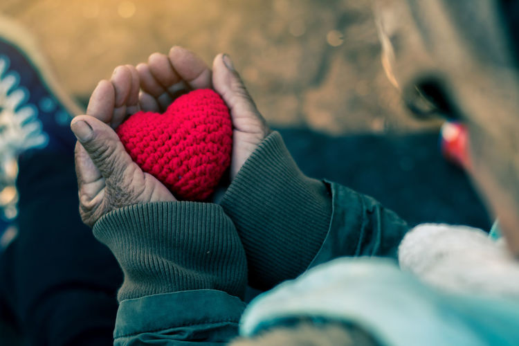Close-Up Of Hand Holding Heart Shape Knitted Wool