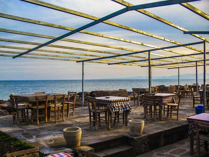 Tables and chairs in cafe by sea against sky