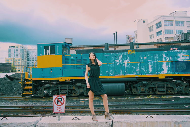 Full length of young woman standing against train in city