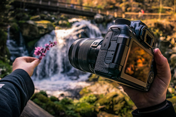 Cropped hand holding camera against waterfall