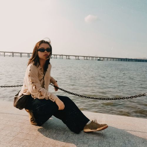 A young woman fighting depression, wearing sunglasses, facing sky and sea breeze.