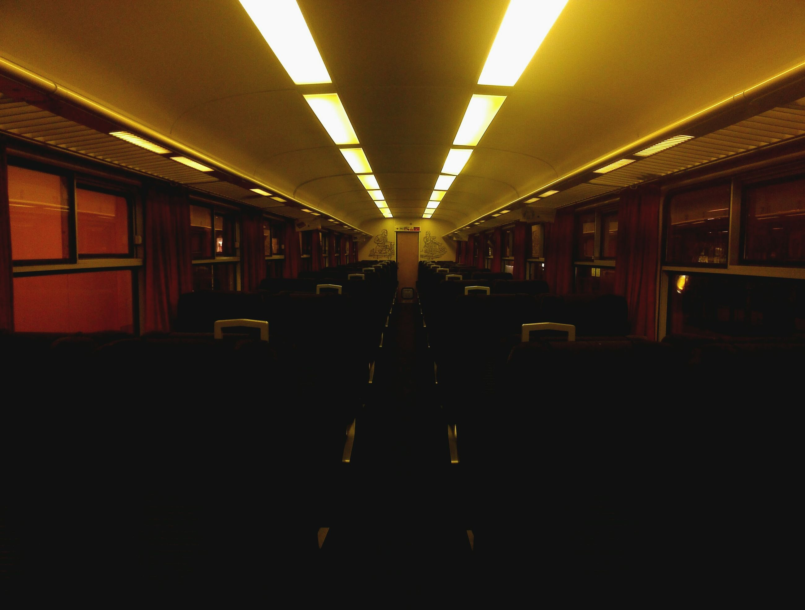 indoors, transportation, illuminated, mode of transport, public transportation, railroad station platform, architecture, built structure, railroad station, travel, empty, train - vehicle, rail transportation, window, train, vehicle seat, passenger train, dark, public transport, interior