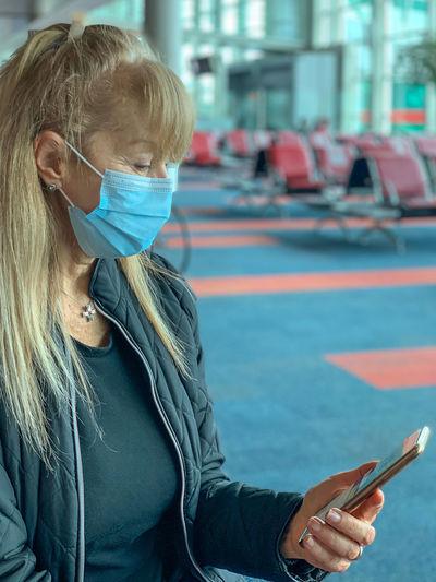 Senior woman wearing mask using smart phone outdoors