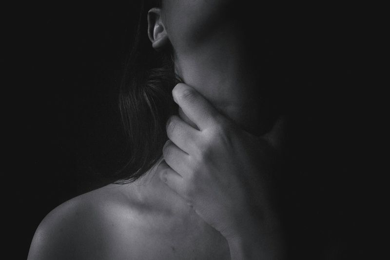 Midsection of topless woman choking throat against black background