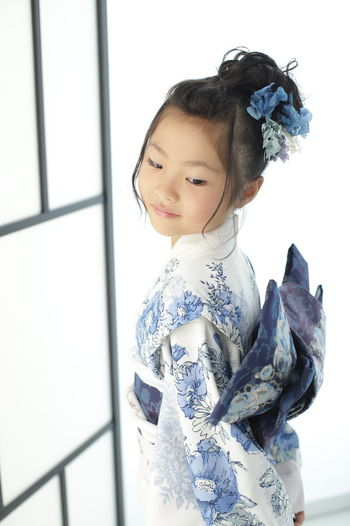 Side view of cute girl wearing traditional clothing standing at home
