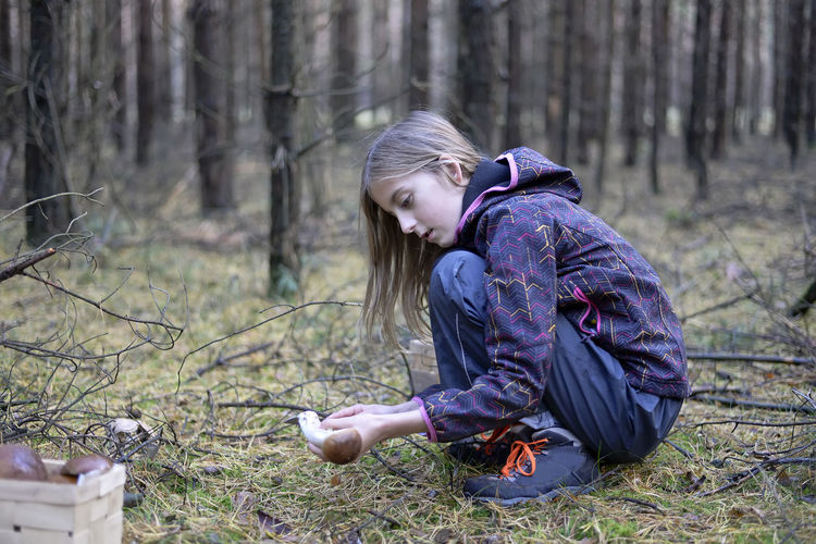 Side View Of Cute Girl Collecting Edible Mushroom In Forest