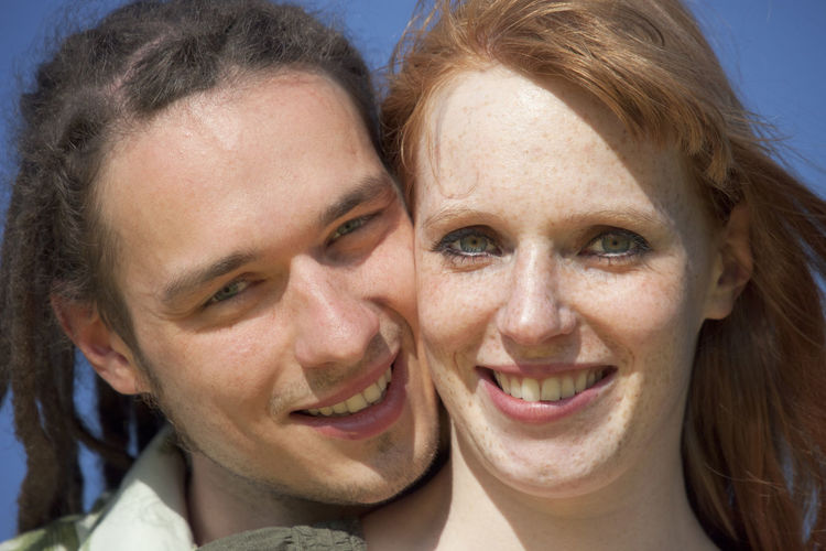 Close-up portrait of smiling young couple